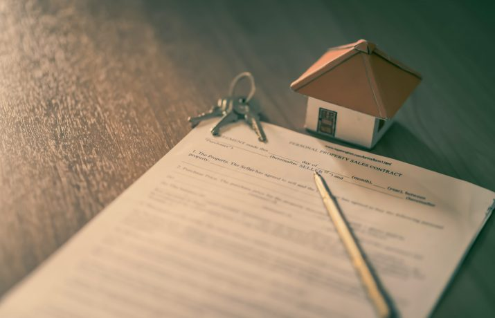 Um contrato com chaves, em cima de uma mesa, lápis e uma casa em miniatura/maquete.