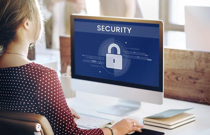 Mulher trabalhando em seu computador com aviso de segurança